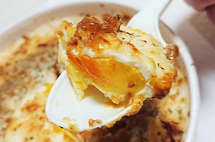 「玉子と食べる!ミートソースドリア」の玉子をスプーンですくった写真
