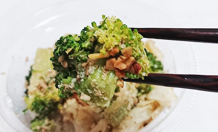 「国産ブロッコリーとキャベツのごま和えサラダ」のブロッコリーを箸でつまんだ写真