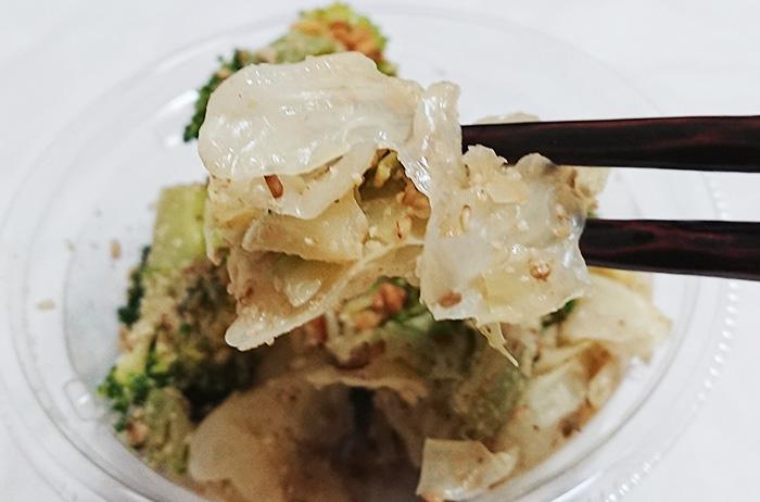 「国産ブロッコリーとキャベツのごま和えサラダ」のキャベツを箸でとりあげた写真