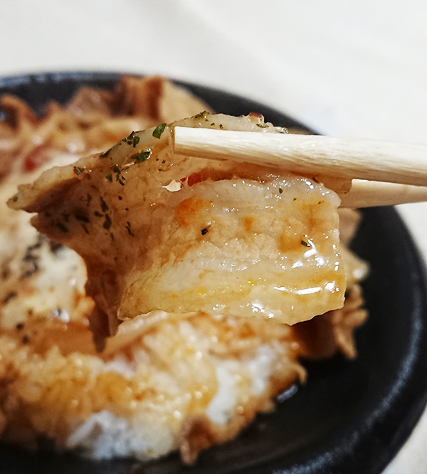 「イタリアンポークジンジャー丼」の豚肉を箸で持ち上げて撮った写真