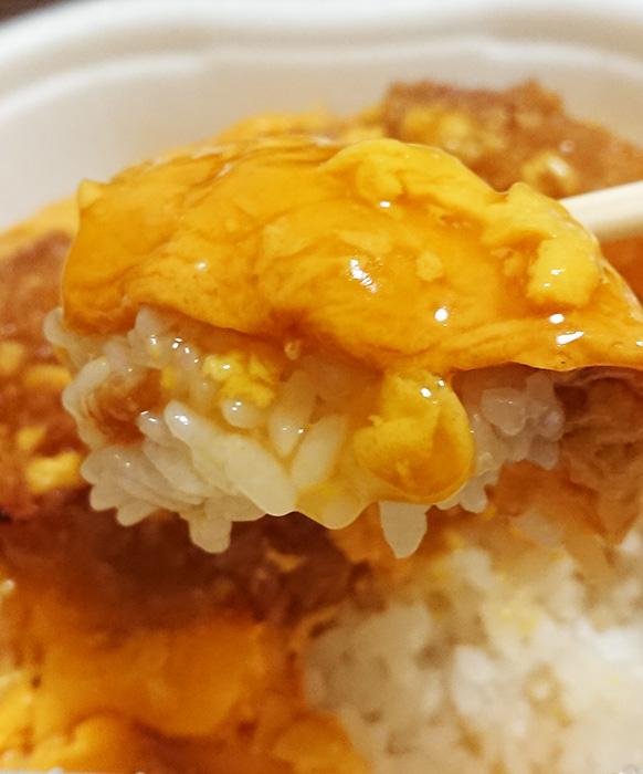 「お肉たっぷり!特製ロースかつ丼」のタマゴとご飯を箸で持ち上げた写真