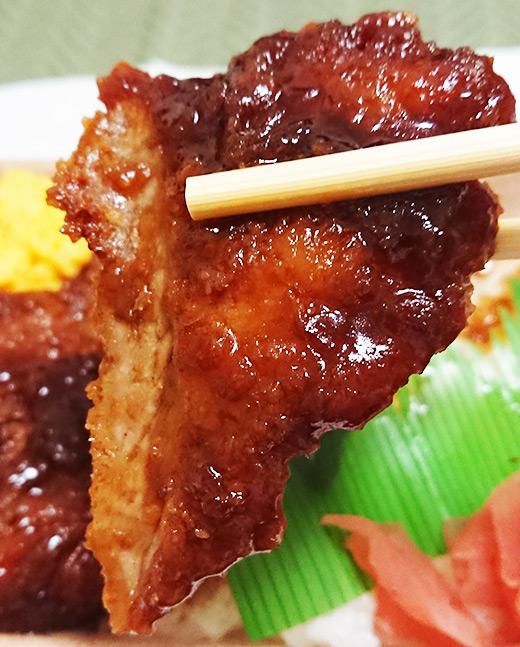 「ソースひれかつ御飯」のヒレカツを箸でつかんでアップで撮った写真