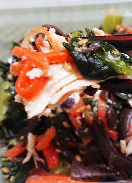 「小松菜と国産ケールのナムルサラダ」の具材を箸でつかんで撮った写真