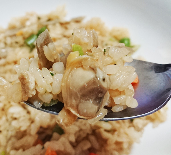 『あさりごはん(冷凍)』のご飯をスプーンですくった写真