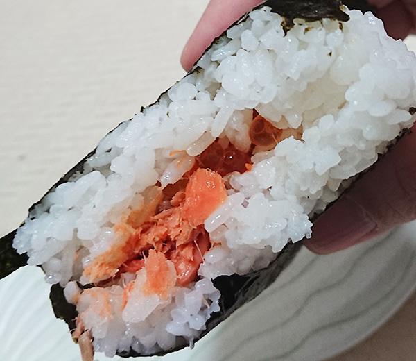 『大きな手巻おにぎり 紅鮭といくら』のおにぎりを半分に割った写真