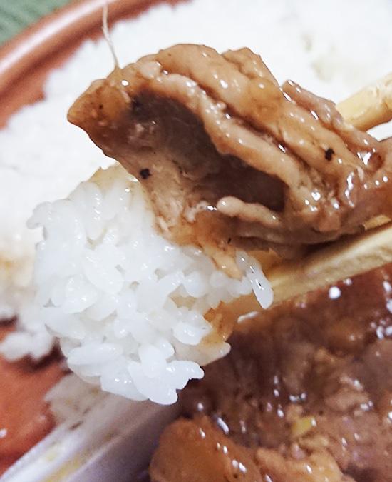 「香ばし炒めの生姜焼きプレート」の肉とご飯を箸でつまんだ写真
