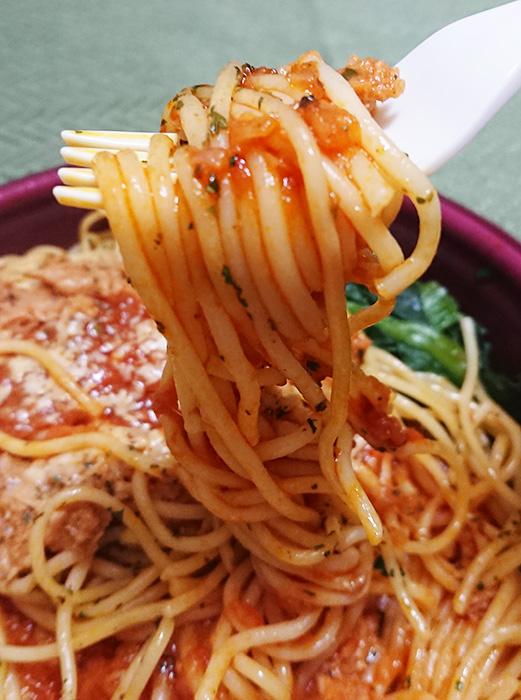 「ツナとほうれん草のトマトソースパスタ」の麺をフォークで持ち上げた写真