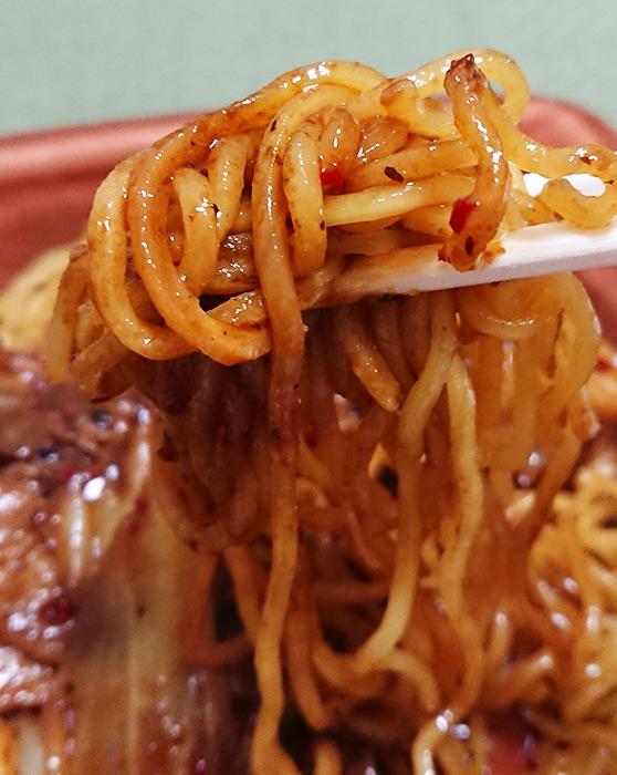「辛さ後引くホイコーロー焼そば」の麺を箸で持ち上げて撮った写真