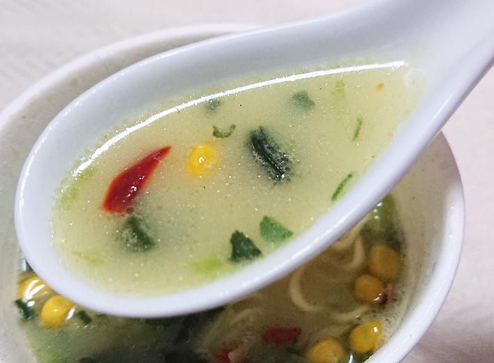 「ほうれん草たくさん ミルク仕立て塩ラーメン」のスープをレンゲですくった写真